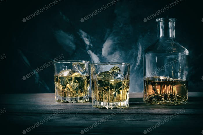 Decanter and two glasses of whiskey on marble background