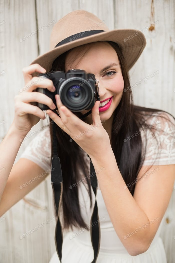 Pretty brunette taking a photo against bleached wooden planks