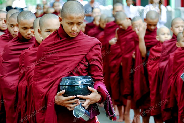 AMARAPURA, MYANMAR - JUNE 28, 2015: Buddhist monks queue for lunch in Myanmar