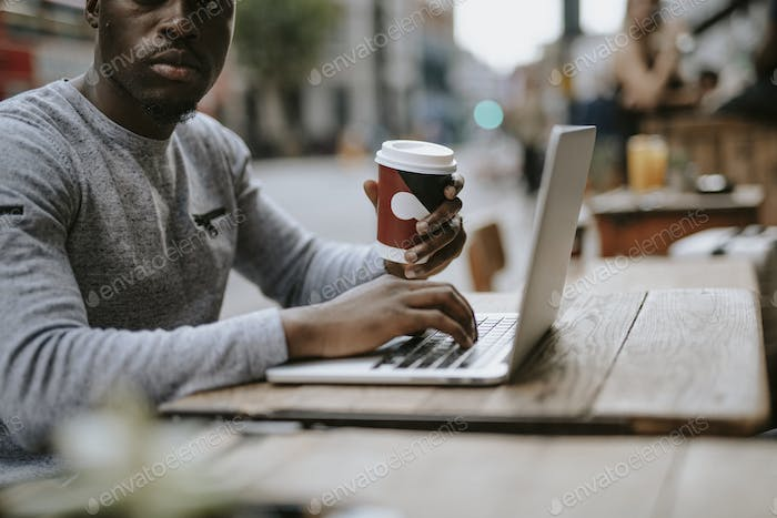 Man working on a laptop at a cafe