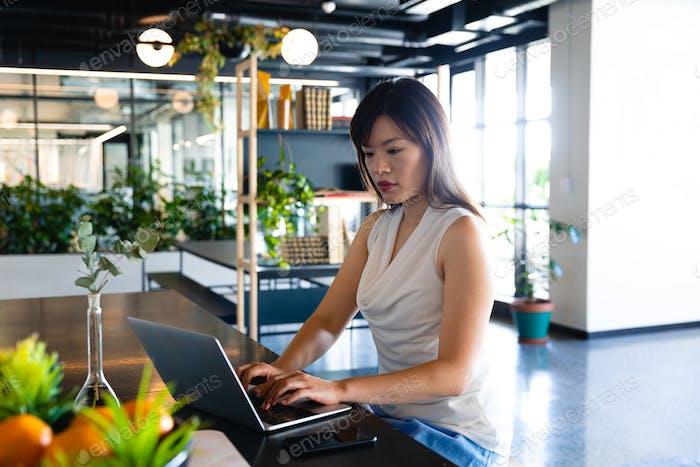 Asiatische Frau arbeitet auf ihrem Laptop in modernen Coworking Zone