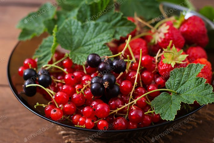Plate with fresh berries (strawberries and currants) on dark wooden background