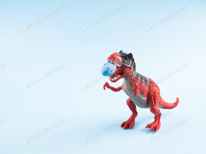 Angry dinosaur toy with easter egg in mouth
