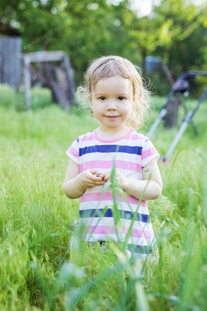 Glückliches kleines Mädchen stehend in hohem Gras