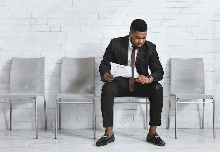 Serious black businessman with resume waiting for work intrview, looking at his wristwatch in
