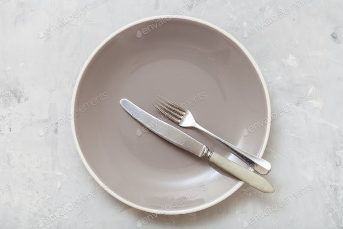 top view of gray plate with flatware on concrete