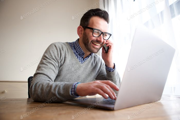 smiling businessman talking on cellphone and working on computer