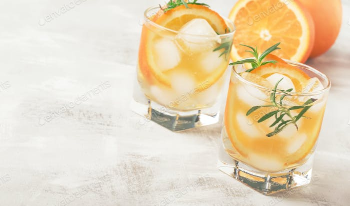 Cold summer drink with mineral water, ice, orange and rosemary
