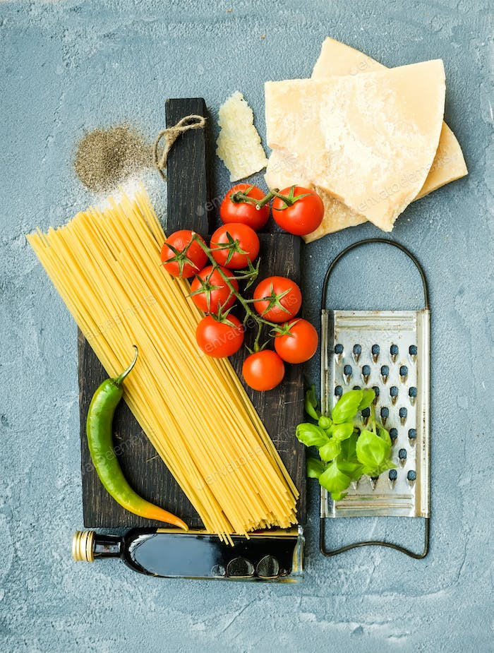 Ingredients for cooking pasta. Spaghetti, Parmesan cheese, cherry tomatoes, metal grater