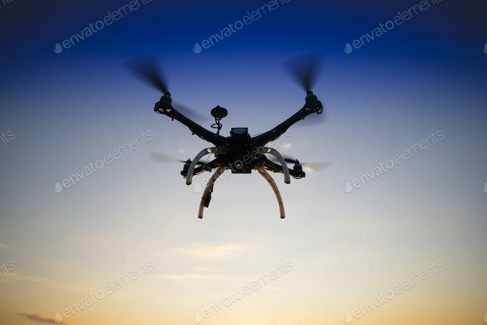 Quadrocopter in flight at sunset