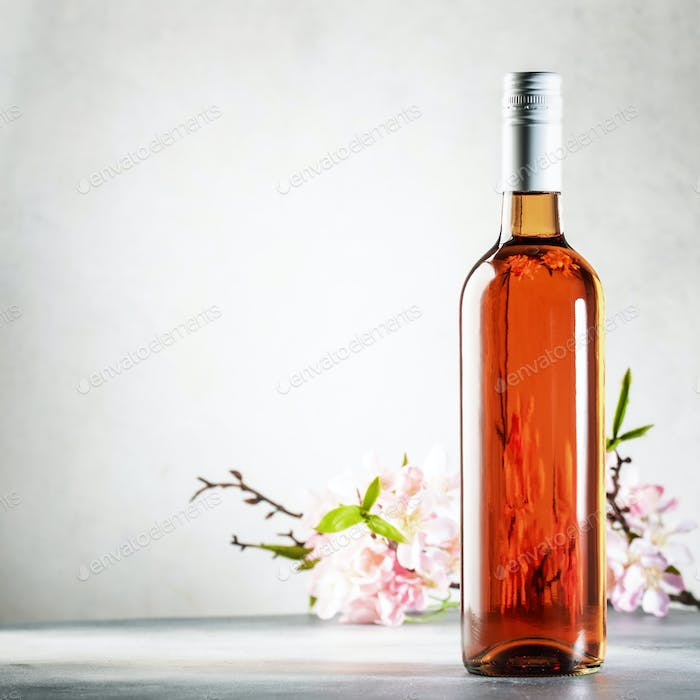 Rose wine bottle on the gray table and spring pink flowers. Rosado, rosato or blush wine