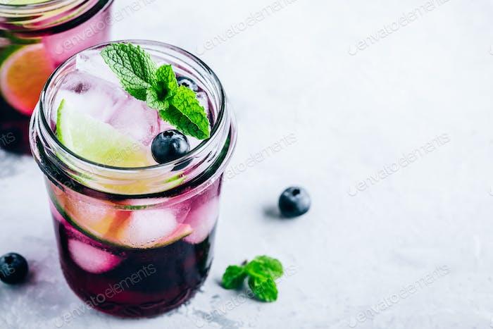 Blueberry Mojito mit Limette und frischer Minze. Eiskaltes Sommergetränk im Glas.