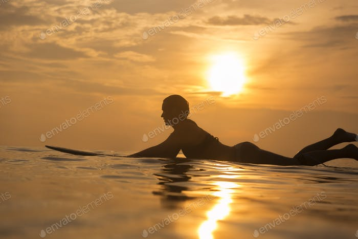 Surfer girl in ocean at sunset time