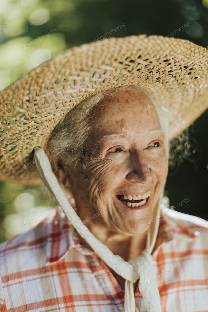 Porträt einer glücklichen Senior Frau mit einem Strohhut