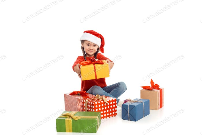 little child in santa hat with christmas gifts, isolated on white