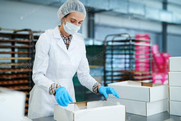 Confectionery factory worker preparing package