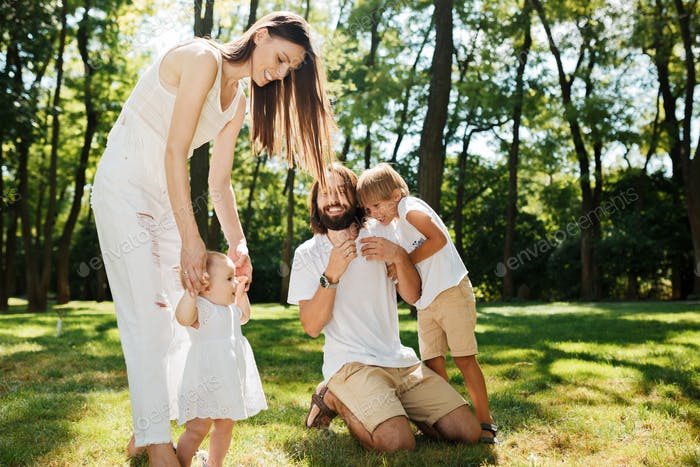 Young dark-haired mother and father dressed in white clothes are spending summer day with kids on a