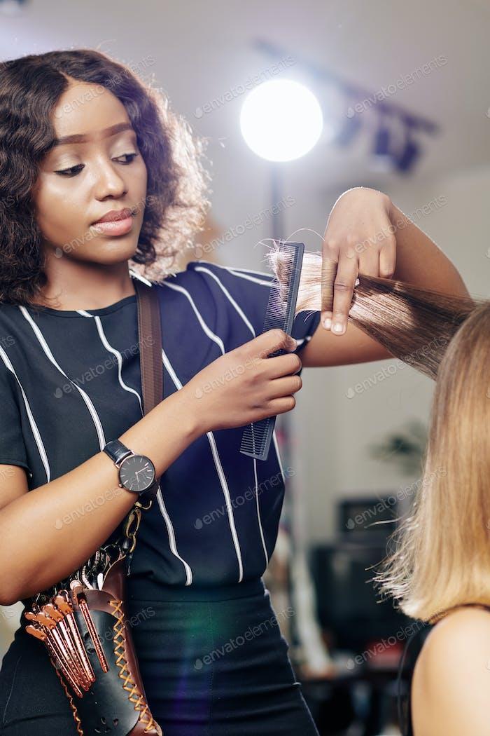 Hair stylist brushing hair section