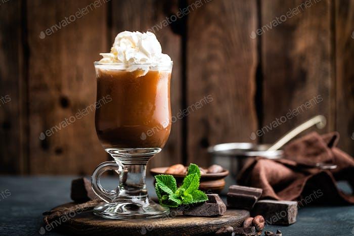 Eiskakaogetränk mit Schlagsahne, kaltes Schokoladengetränk, Kaffee-Frappe auf dunklem Hintergrund