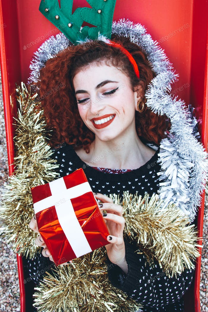 Beautiful redhead young woman with christmas stuff
