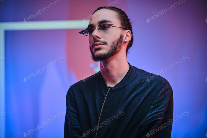 Calm and relaxed young caucasian man standing in a bright studio with neon lights on the background