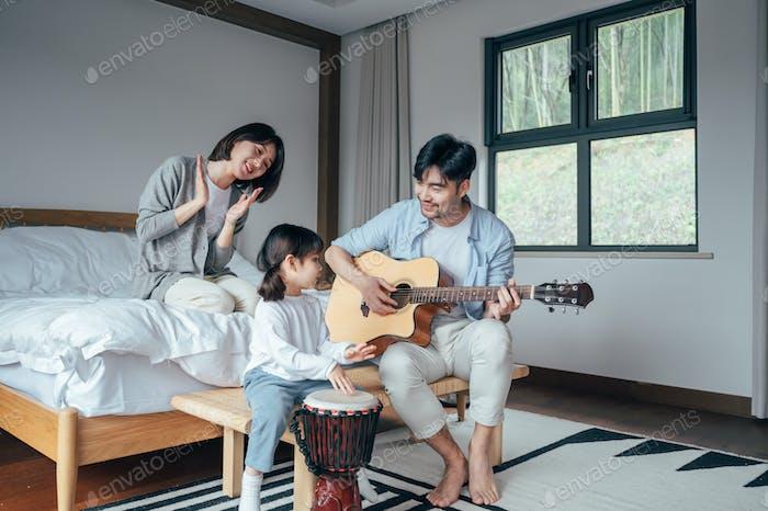Счастливая семья играет на инструментах в спальне