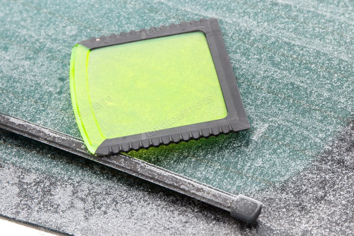 Green ice scraper on window of car, winter problems in transportation