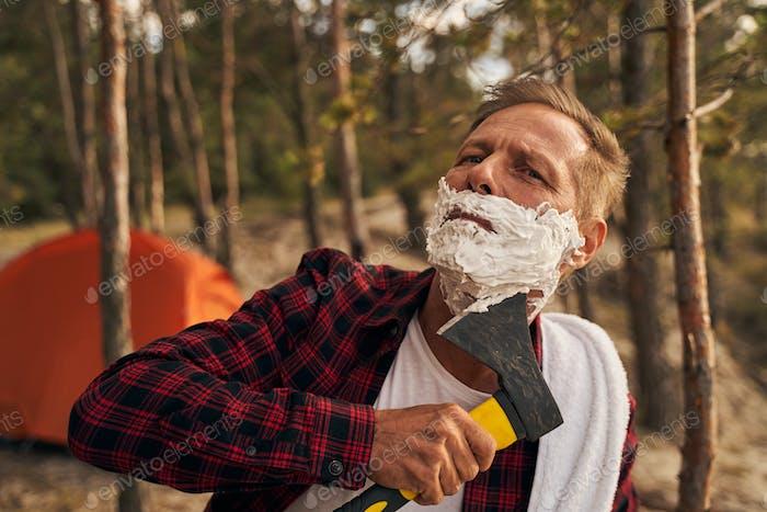 Man using hatchet for shaving in nature