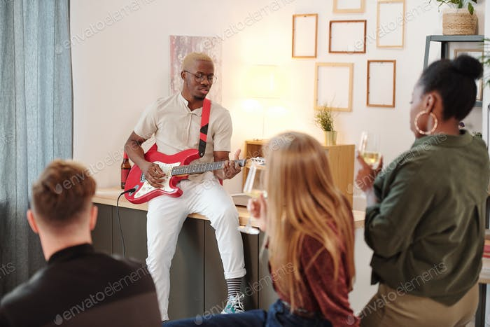 Young intercultural friends listening to singing of African guy playing guitar