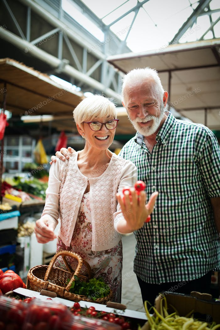 Senior family couple choosing bio food fruit and vegetable on the market during weekly shopping