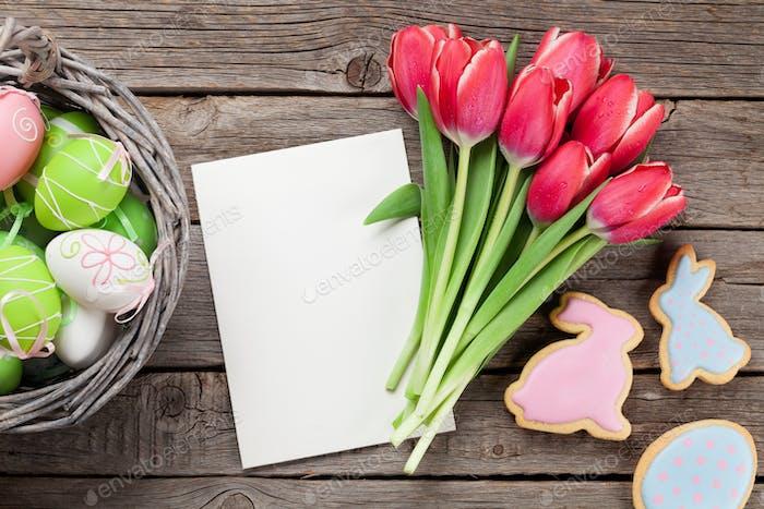 Rote Tulpenblüten und Osterplätzchen und Eier