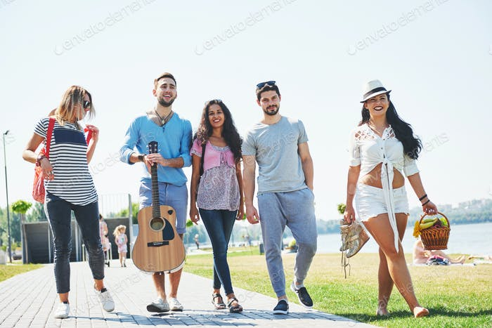 Gemischte Gruppe von Freunden zu Fuß am Strand am Sommertag