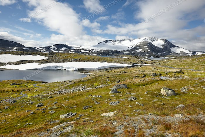 Norwegian rocky mountain landscape with lakes and snow. Norway trekking. Horizontal