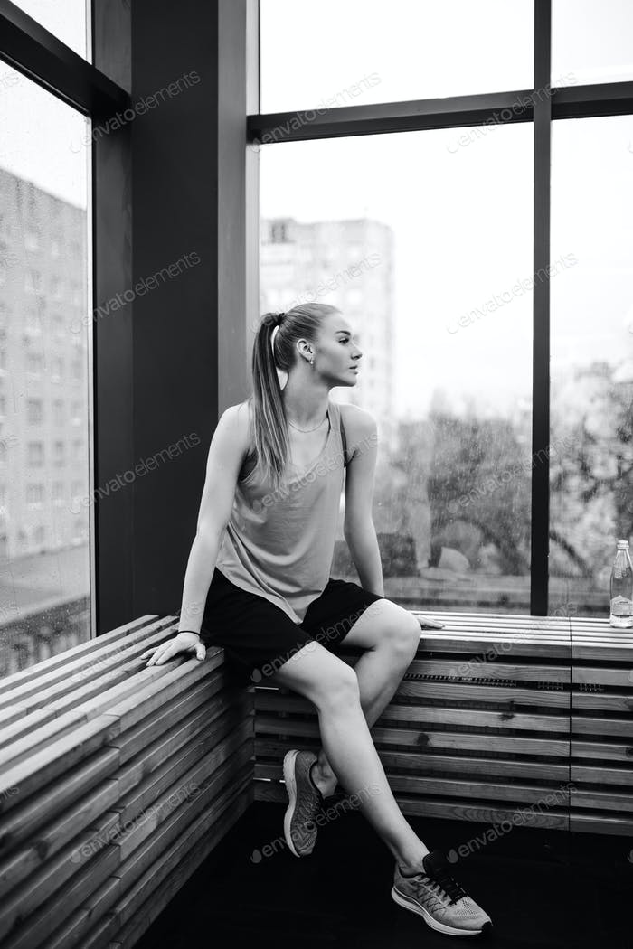 Black and white photo of the athletic girl dressed sport shorts and t-shirt is sitting on the wooden