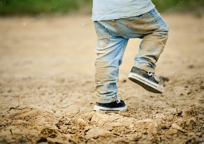 Detail of little boys legs in mud