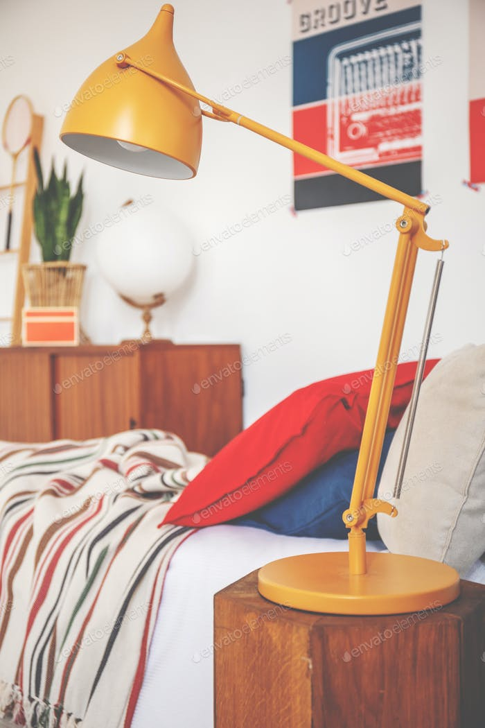 Yellow lamp on wooden stool next to bed with red pillow in teena