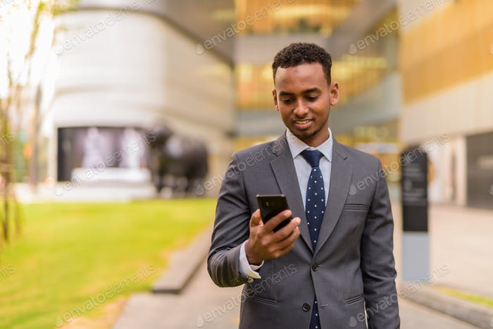 Happy African businessman outdoors smiling and using phone