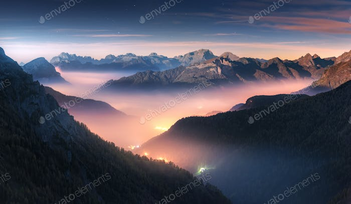 Mountains in fog at beautiful night in autumn in Dolomites, Italy