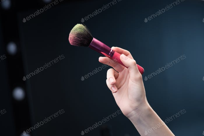 Close-up partial view of female hand holding make-up brush with blusher on it