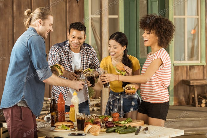 multiethnic friends clinking with glasses of cola at picnic on patio