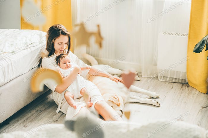 mother with a baby girl and a cute Labrador at home