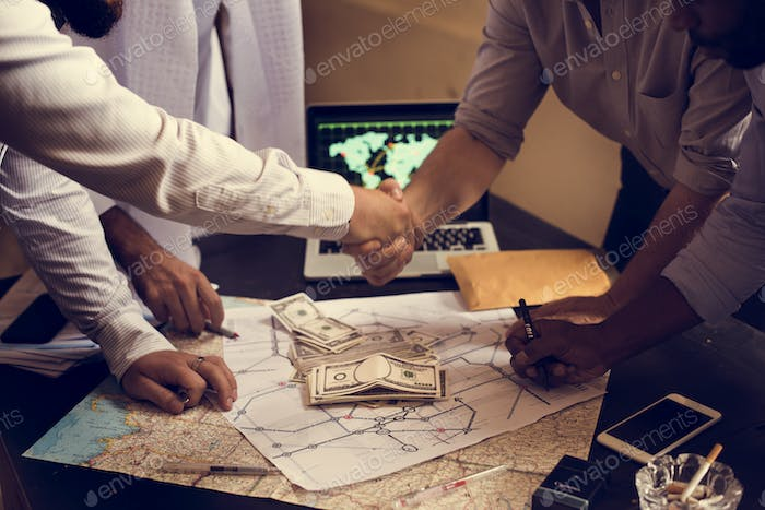 Group of people making agreement handshaking over map and money