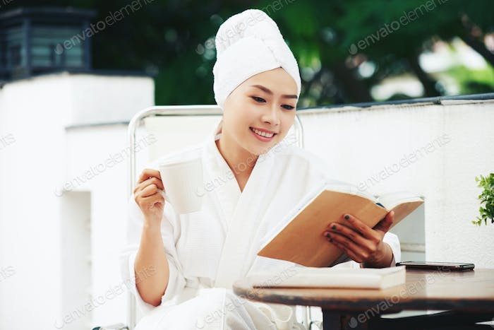 Chilling woman in bathrobe reading book with coffee