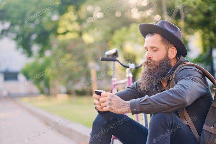 Мужчина сидит на ступеньке над городским парком.