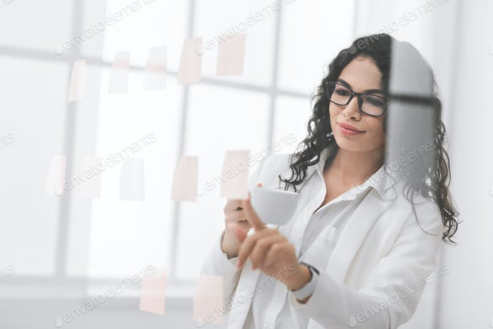 Hispanic businesswoman looking at sticky notes on glass wall