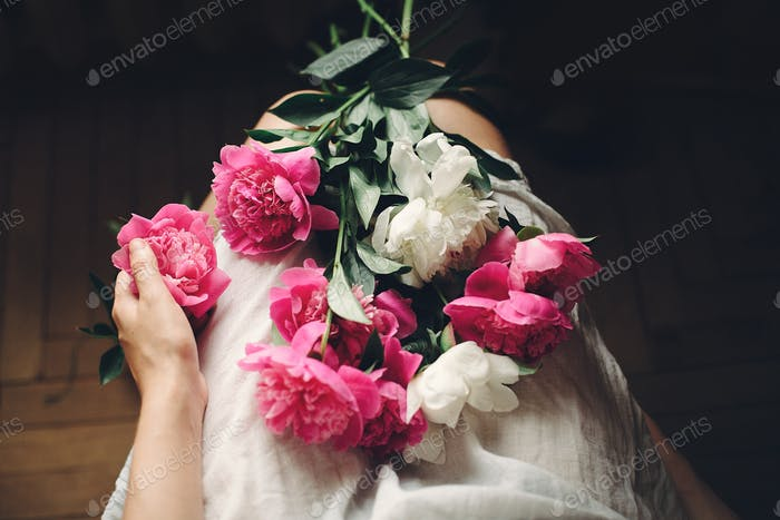 boho girl in white bohemia dress holding beautiful pink peonies on legs