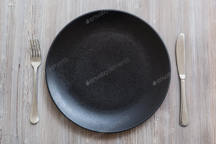 top view of black plate with knife, spoon on gray