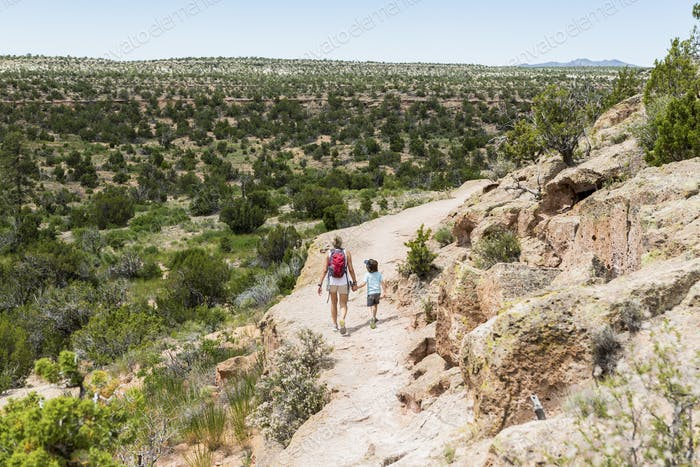 mother and her 5 year old son walking path, Tsankawi Ruins, NM