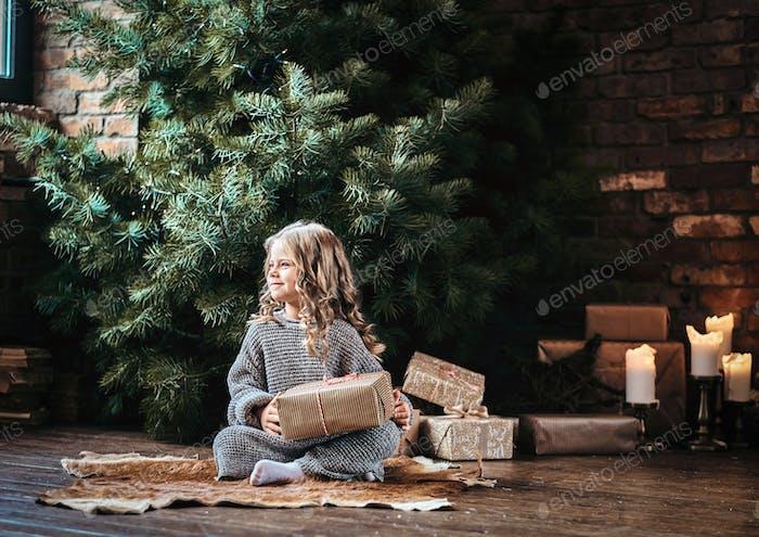 Милая девочка с блондинкой вьющимися волосами сидит на полу рядом с елкой