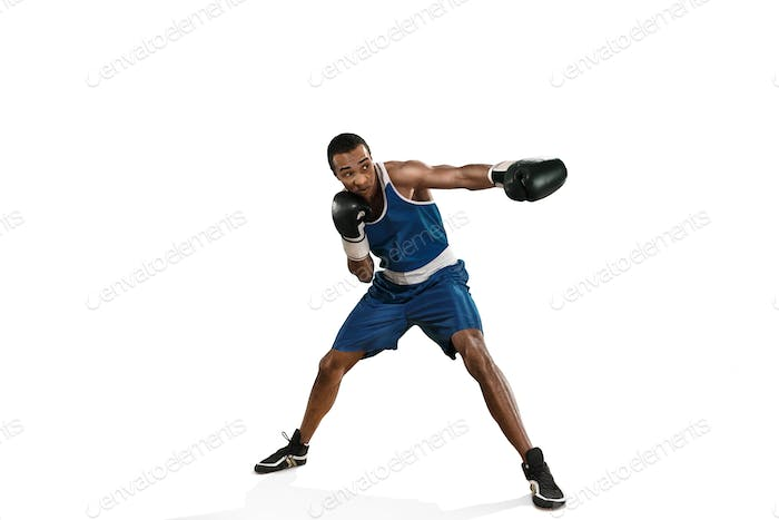 Sporty man during boxing exercise making hit. Photo of boxer on white background